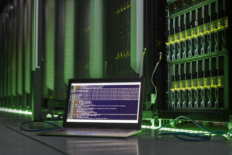 Laptop running Command Line next to server racks