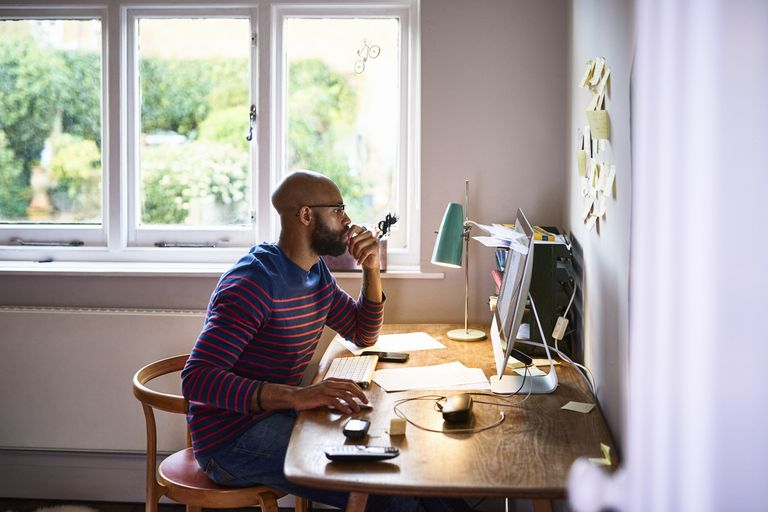 Man in striped shirt sitting at his desk and working on his computer