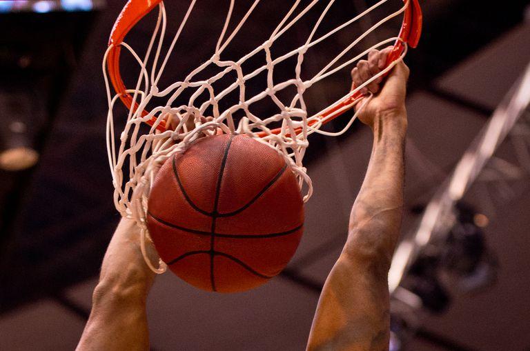 Hands dunking basketball on hoop