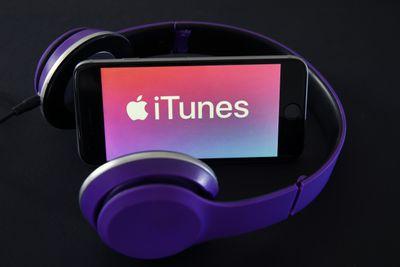 iTunes logo on iPhone with purple headphones