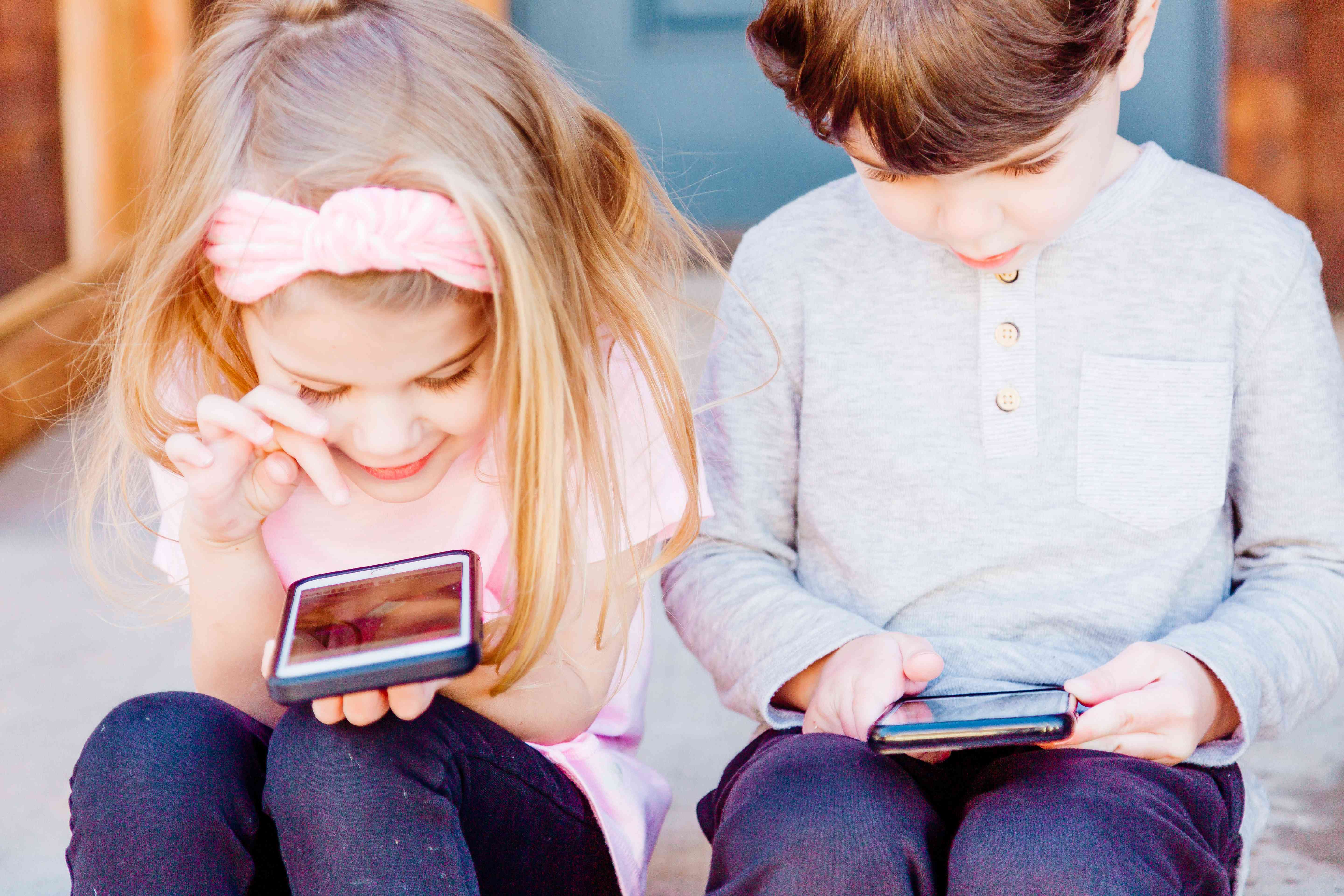 Two young kids using smartphones.