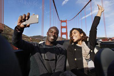 Couple taking in a selfie in a car on the Golden Gate Bridge