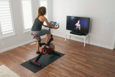 Person streaming iPad from stationary bike to TV