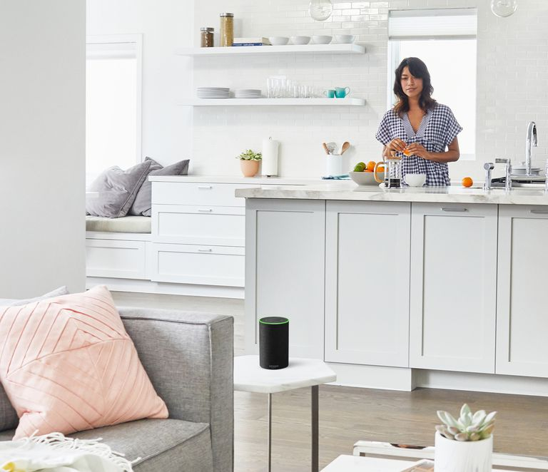 Woman in kitchen looking at Amazon's Echo