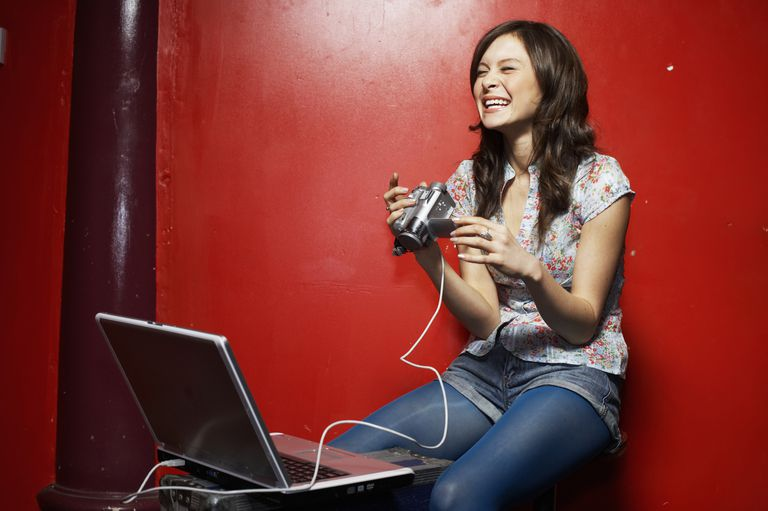 Young woman holding video camcorder connected to laptop, laughing