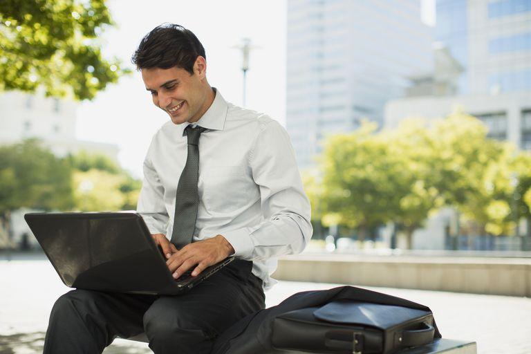 Businessman using laptop outside