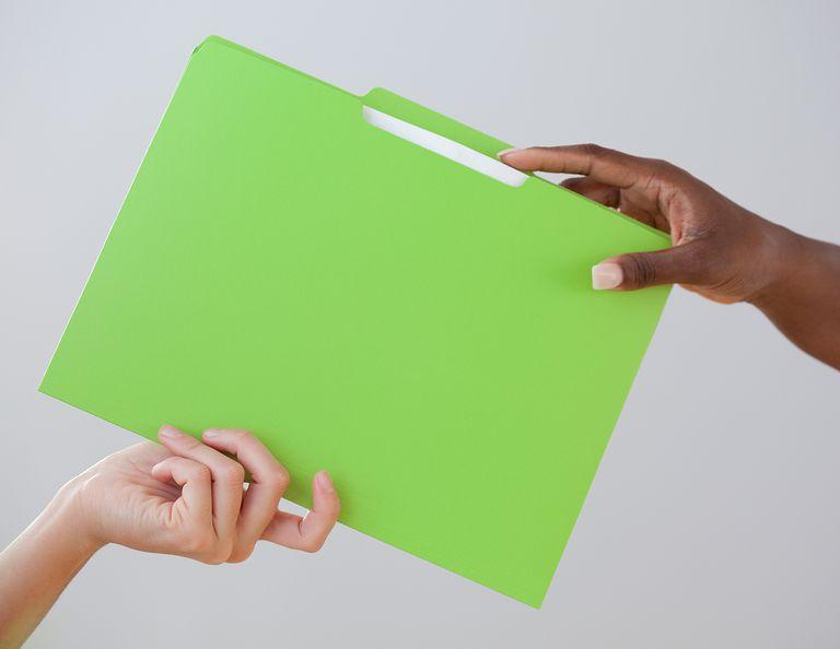 Woman handing co-worker a folder