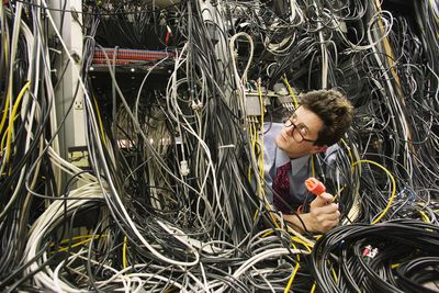 Computer worker buried in network cables, holding plug