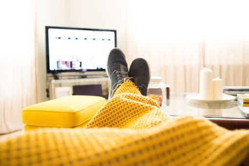 Guy relaxing at home from personal perspective laying in sofa in autumn day covering with blanket while watching television