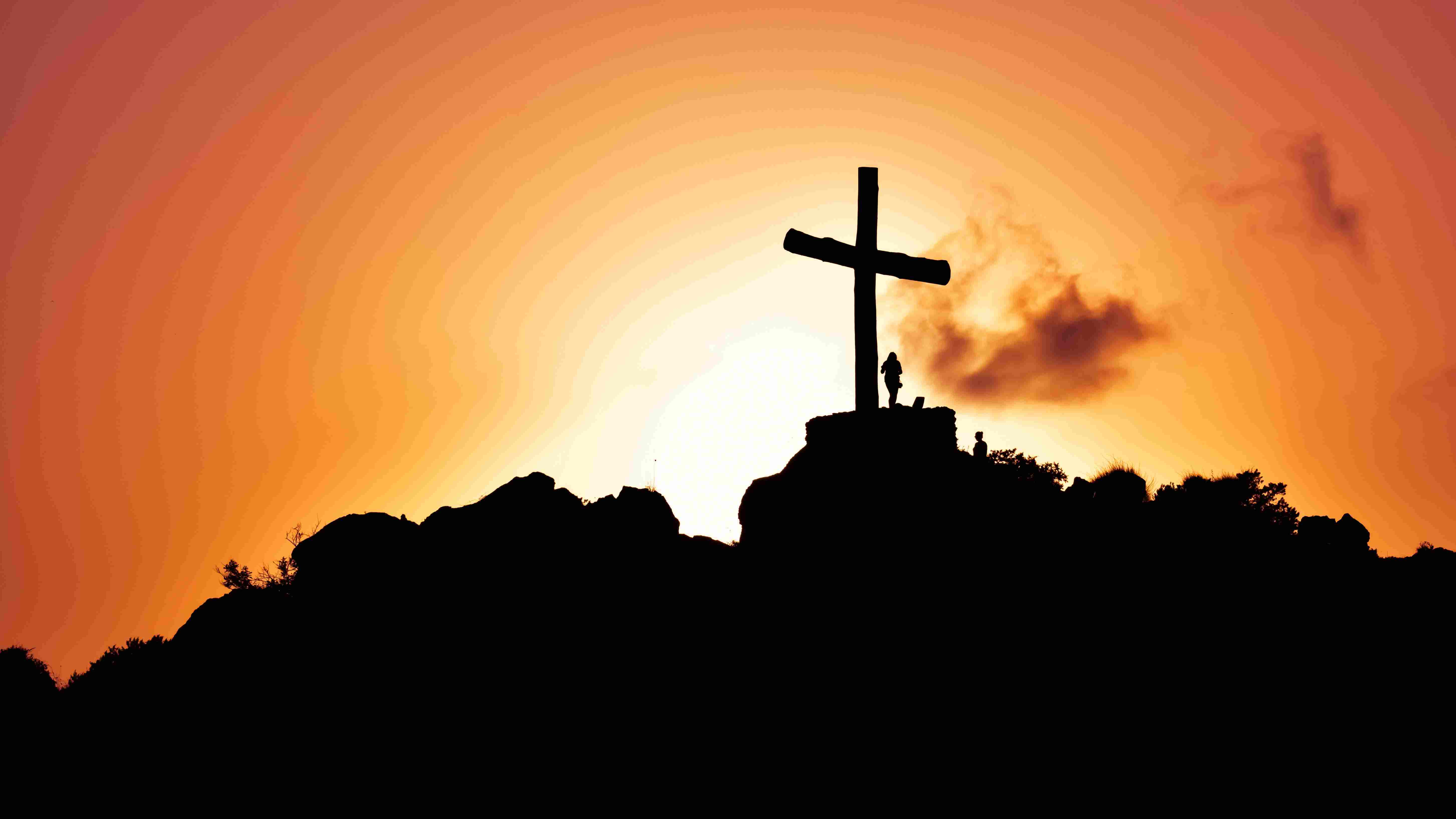 Cross on a hill next to a person backlit by a sunset sky.
