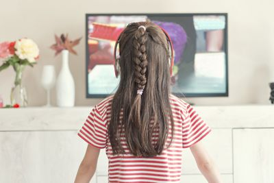 Photo of a girl watching TV using wireless headphones