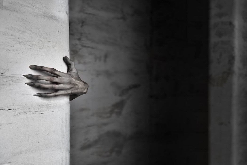 A scary hand with long, dirty nails wrapped around a corner.