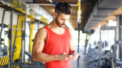 Fit man wearing an orange tank top checking his bodybuilding app on his iPhone in a gym