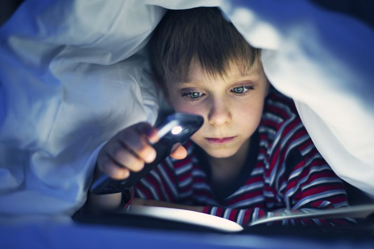 Boy using smartphone flashlight under blanket