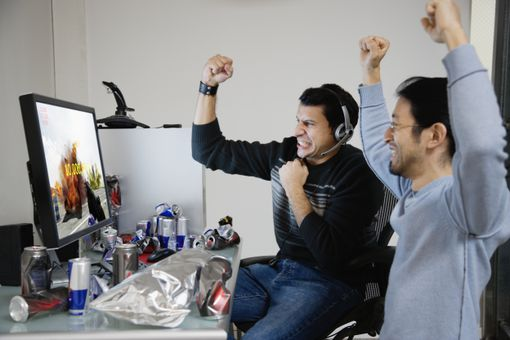 Two men cheering with raised hands, sitting in front of computer