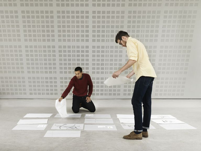 Two men sorting paper on the floor of an office.