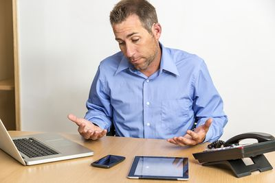 Man shrugs looking at a laptop, smartphone, tablet, and land phone line