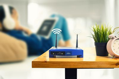 A wireless router and a person using smartphone on living room at home ofiice