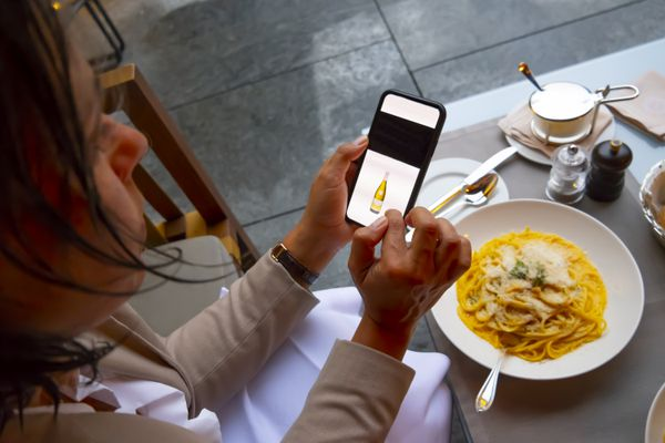Woman looking at an image of a bottle on their smartphone while a bowl of food sits nearby