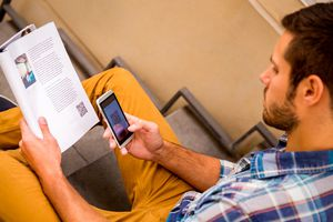 A man reading a QR barcode in a magazine with his smartphone.
