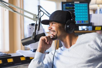 Disc jockey smiling in studio with stereo headphones on by microphone