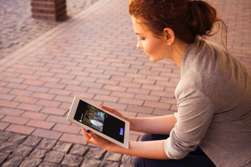 A woman looking at a GIF on an iPad Air tablet.