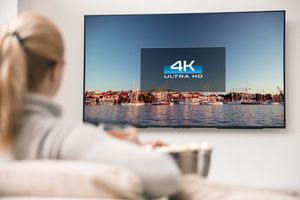 Woman sitting on couch watching 4K Ultra HD TV