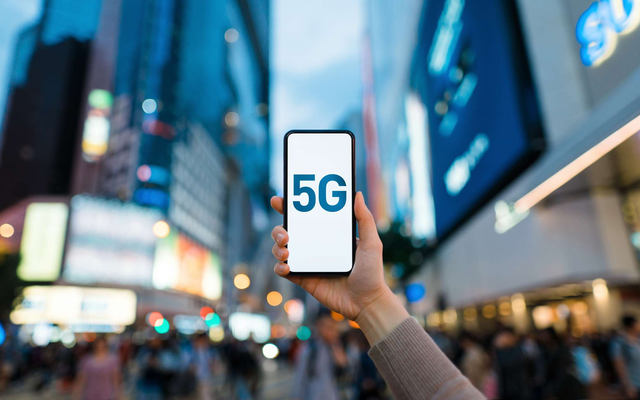Someone holding a smartphone up in a busy city with '5G' displayed on the screen.