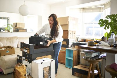 Woman unboxing a printer in a home office