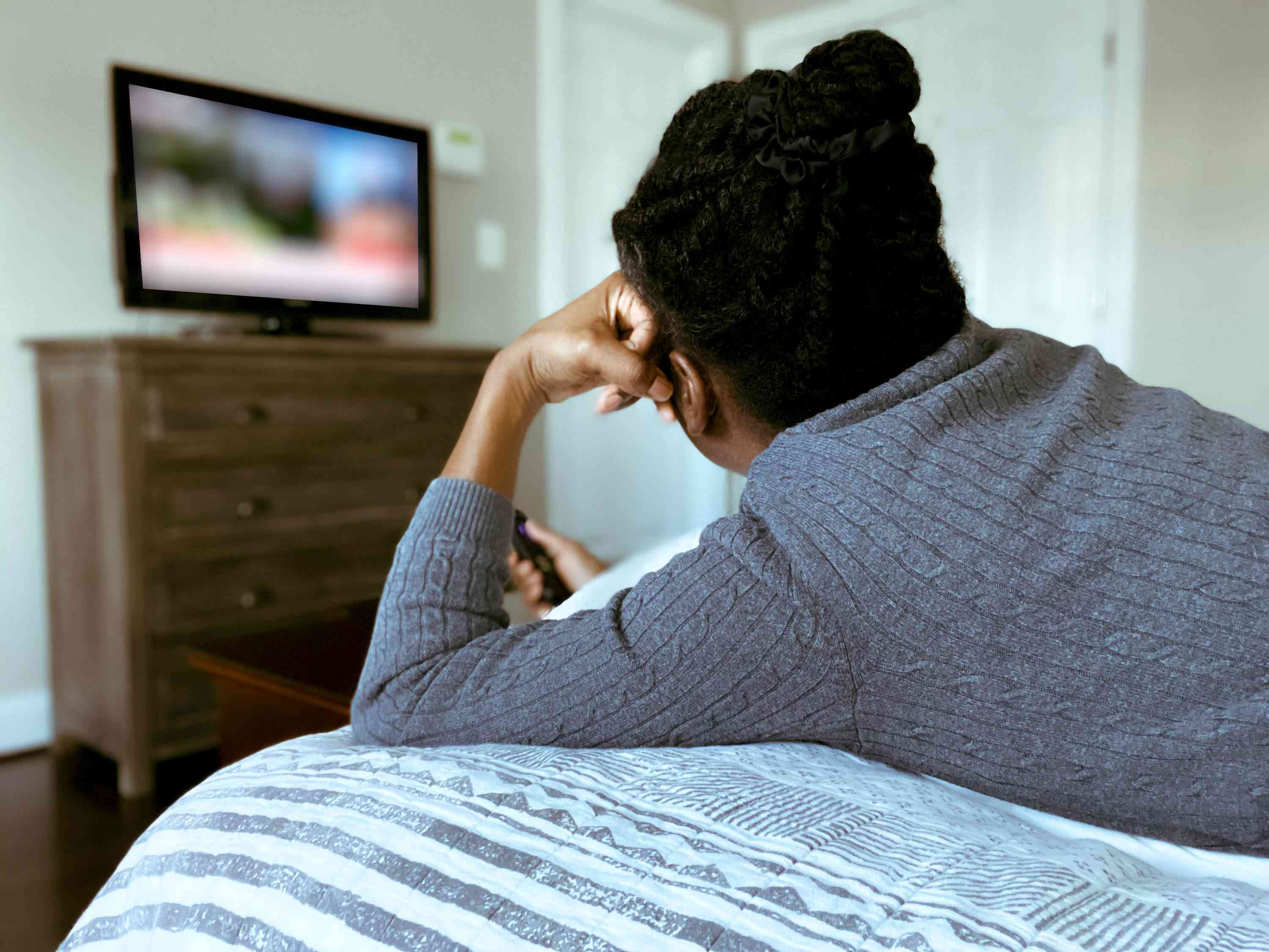 Woman watching TV, from the back shot