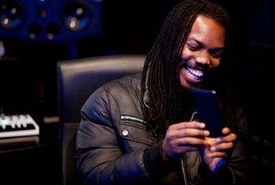 Man laughing while looking at his iPhone screen