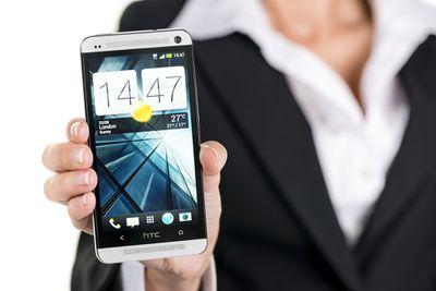 Studio shot of women holding white HTC One