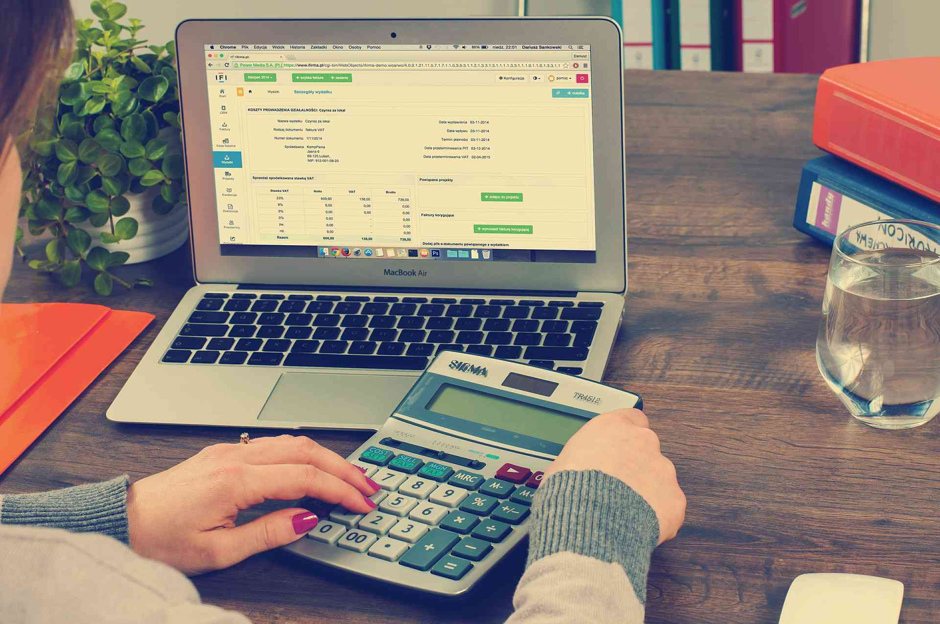 Woman calculating budget using laptop and calculator