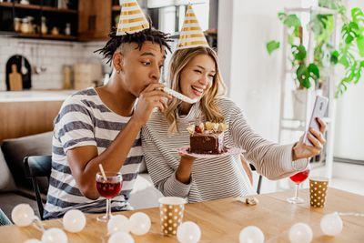 A young couple celebrating their birthday with cake while filming a TikTok on their smartphone.