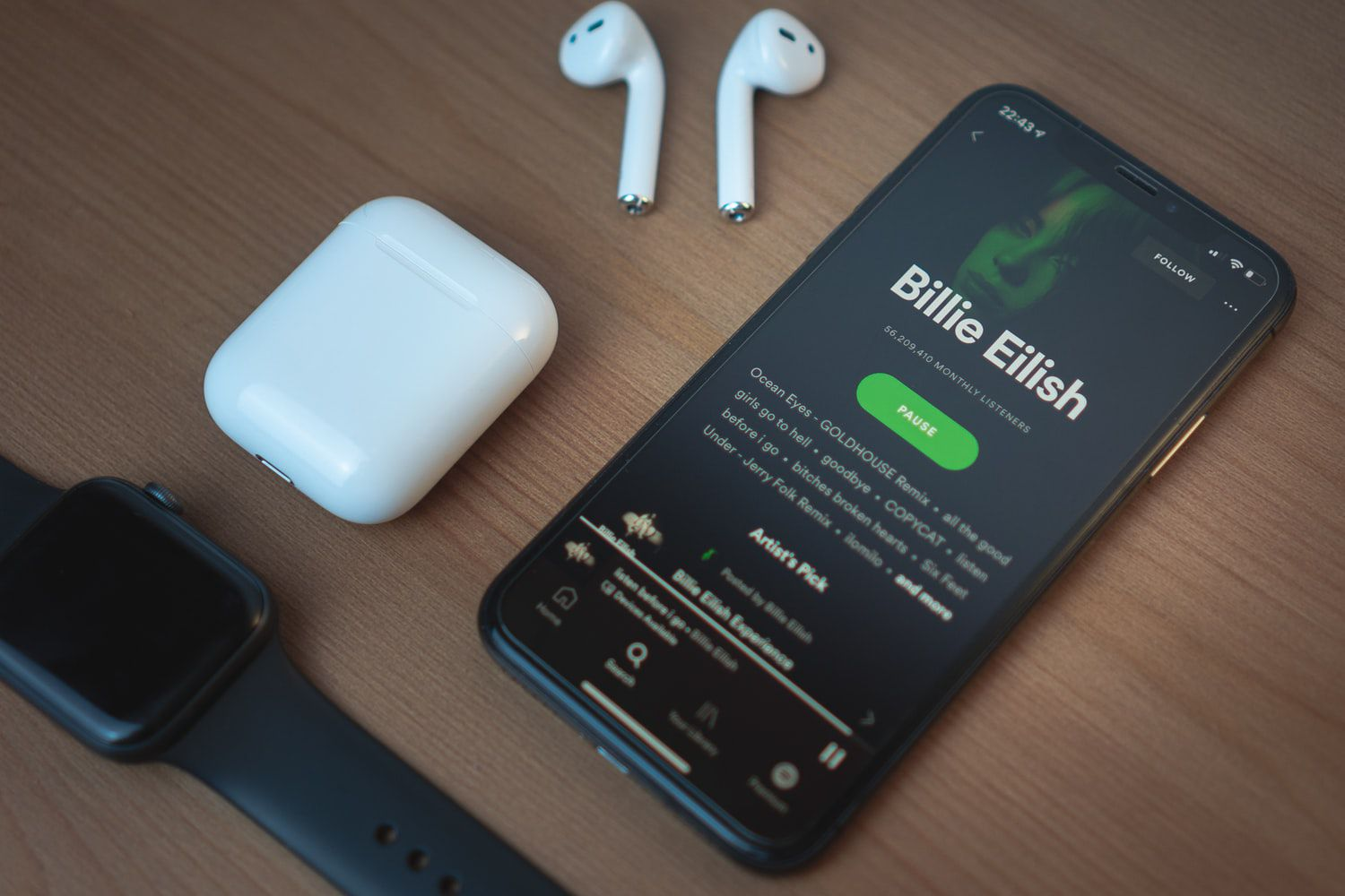 black iPhone showing Spotify on wooden table next to apple watch and AirPods