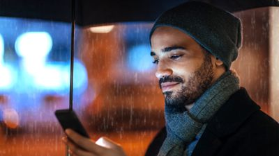 Man standing under an umbrella in the rain checking his Android weather app