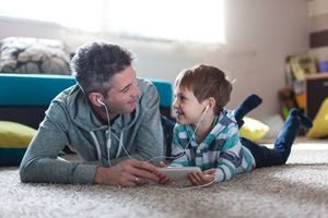 A parent and child listen to a mobile phone with headphones