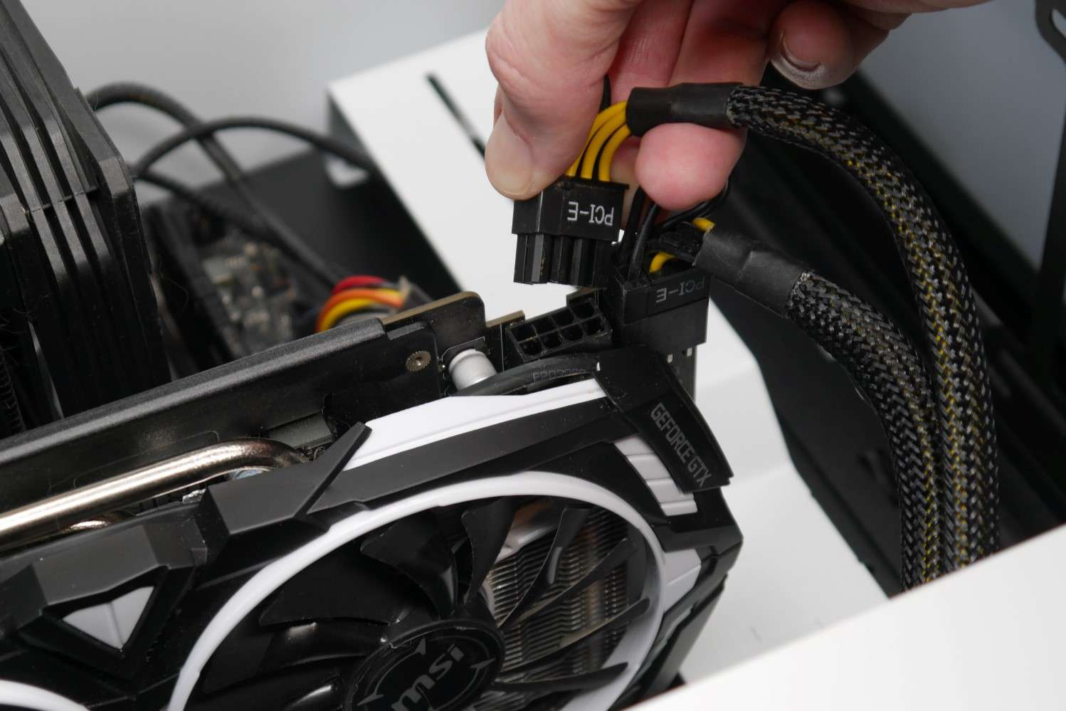 A photo showing a graphics card's PCIe power connector being disconnected