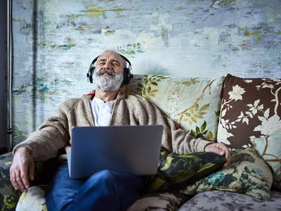A man sitting on a couch with a laptop on his lap and headphones on listening to music