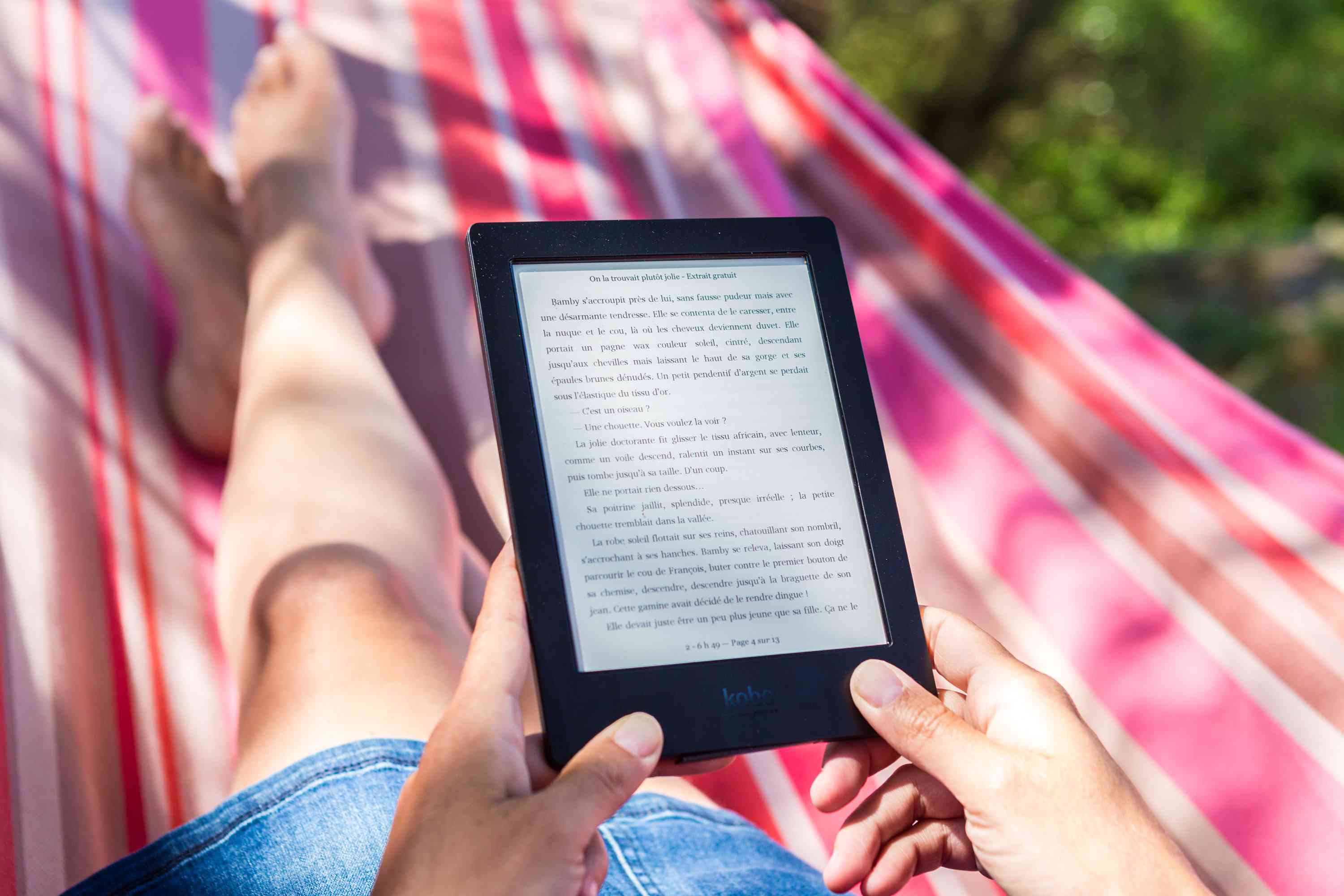 Someone reading on an Amazon Kindle while sitting in a hammock outside.