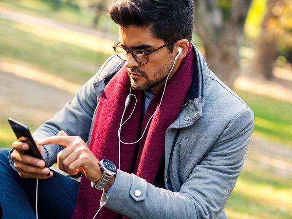 A man wearing glasses listening to a podcast on his smartphone.