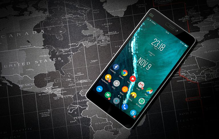 Smartphone laying on black and white world map
