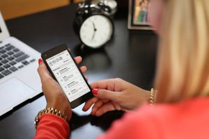 A woman looking at Verizon Parental Controls on her smartphone.