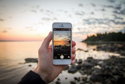 A person holding an iPhone taking a picture of the beach