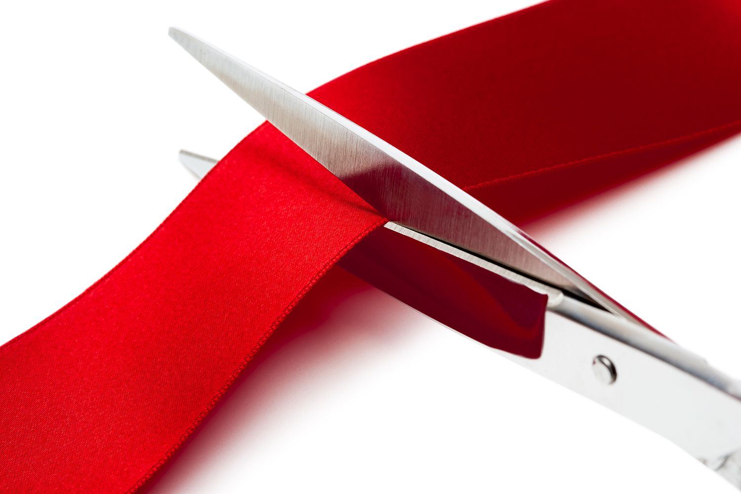 Scissors cutting a red ribbon on a white background.
