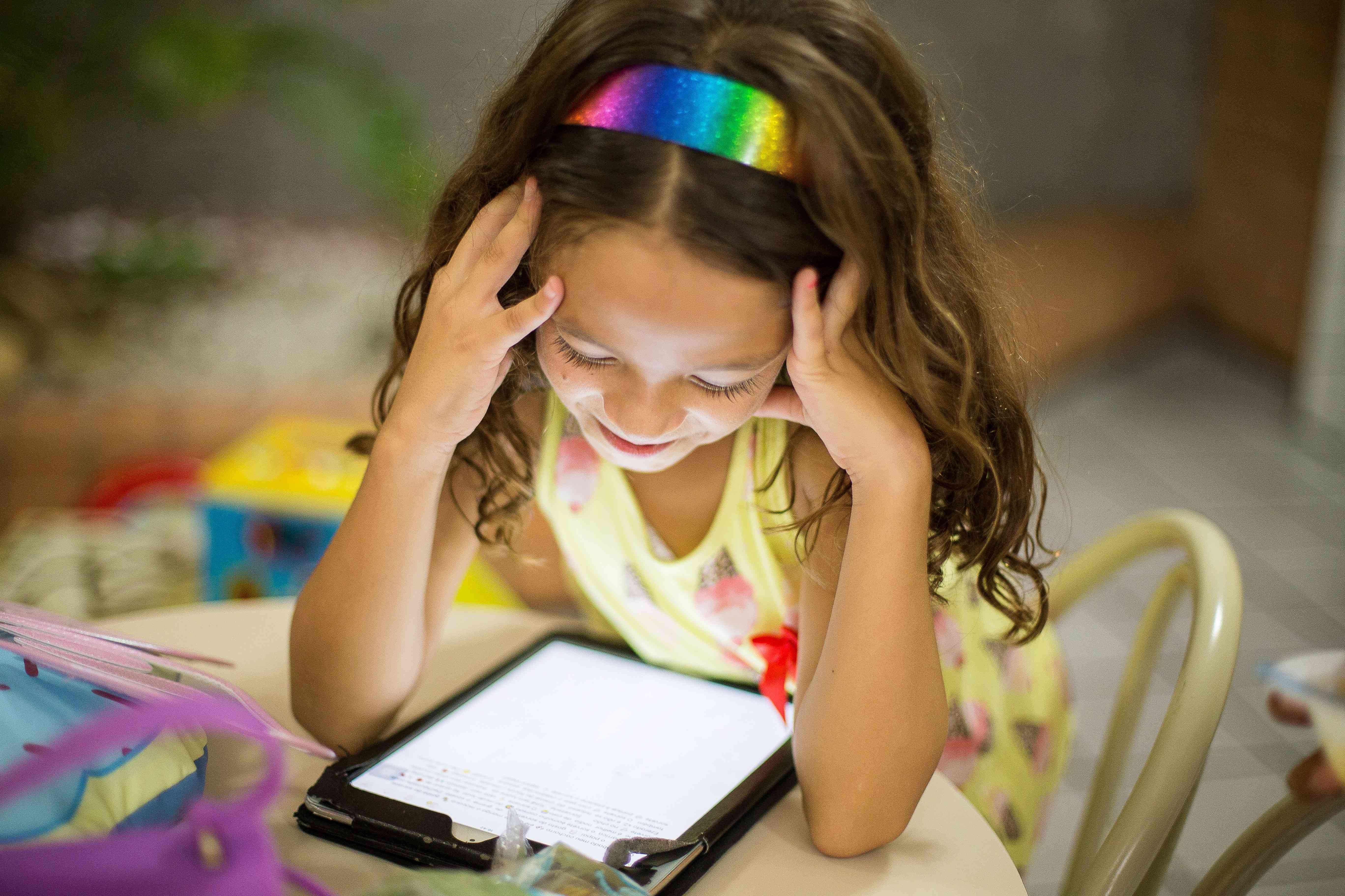 Picture of a young girl reading on a tablet