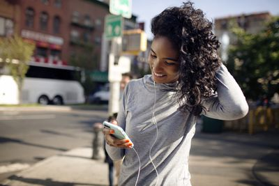 Woman looking at her iPhone and using headphones on a city street