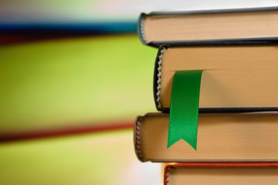 A green ribbon bookmark in a stack of books
