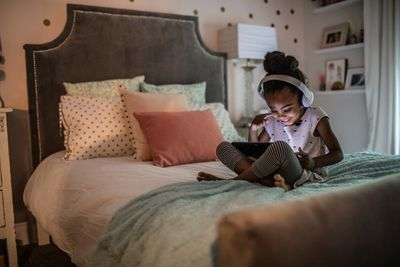 A small girl sitting on her bed with headphones in smiling at a tablet in front of her