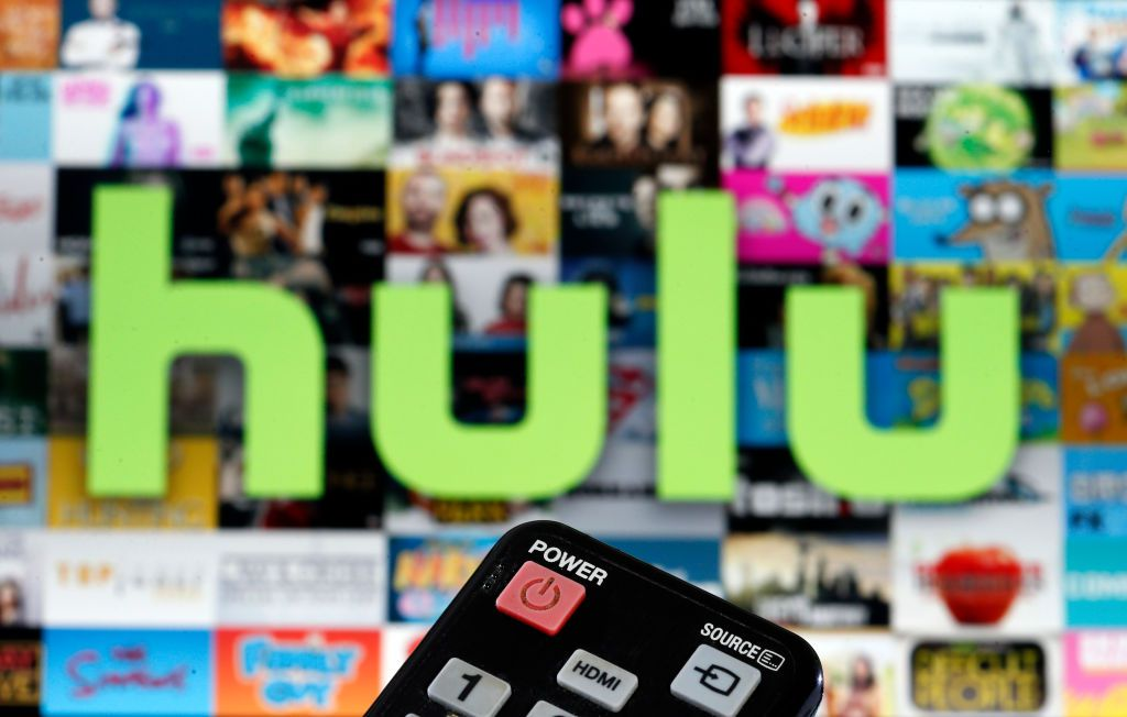 A remote control is seen in front of a television screen showing a Hulu logo.